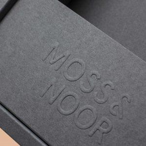Närbild på efterbehandlingen emboss på en grå Moss & Noor förpackning